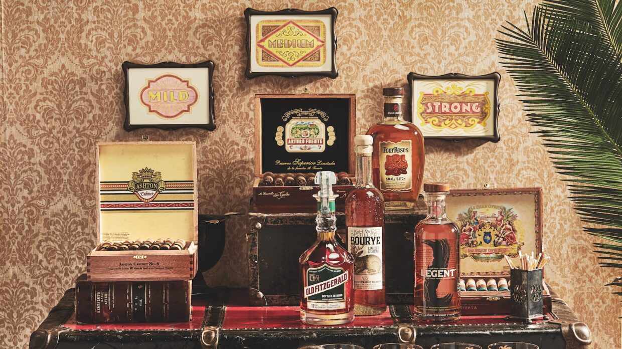 American whiskies displayed on a bar along with open boxes of cigars.