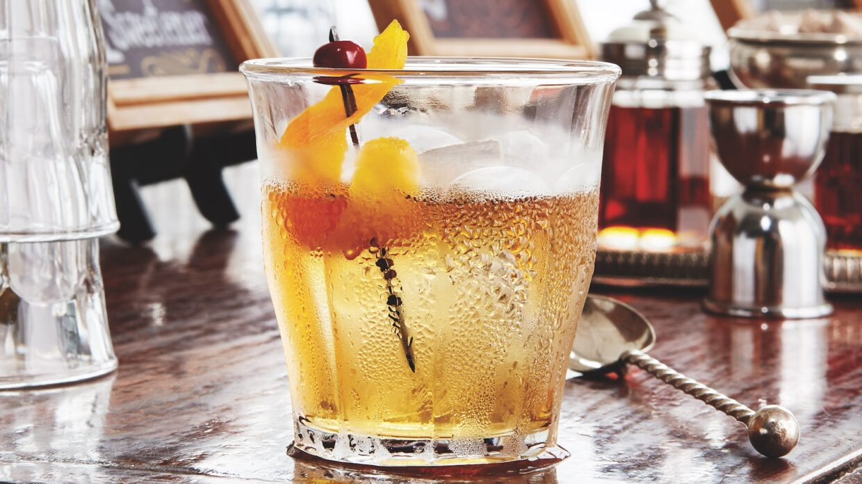 An Old Fashioned in a whiskey glass, showing signs of condensation.