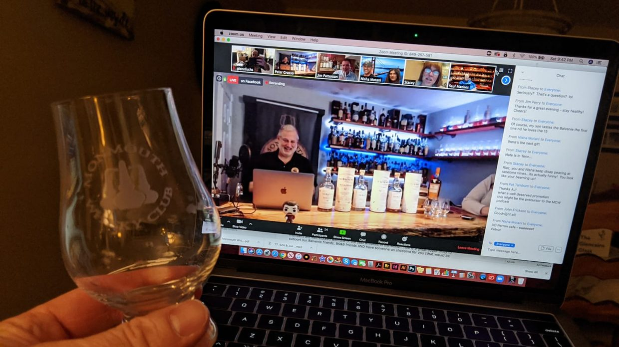 A photo of a laptop screen in which an image of Monmouth Whisky Club co-founder Peter Grasso is visible, seated in front of a laptop of his own, at his home bar, with several bottles of whisky resting on the table beside him.