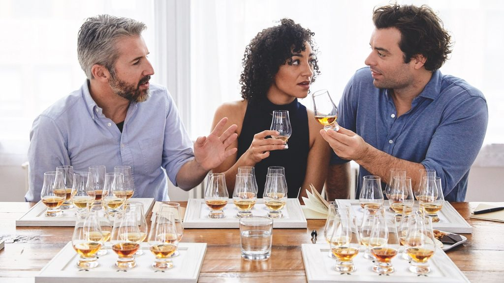 Three friends discuss whisky while in a tasting.