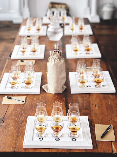 A covered bottle of whisky sits center, surrounded by tasting mats with glasses on them.
