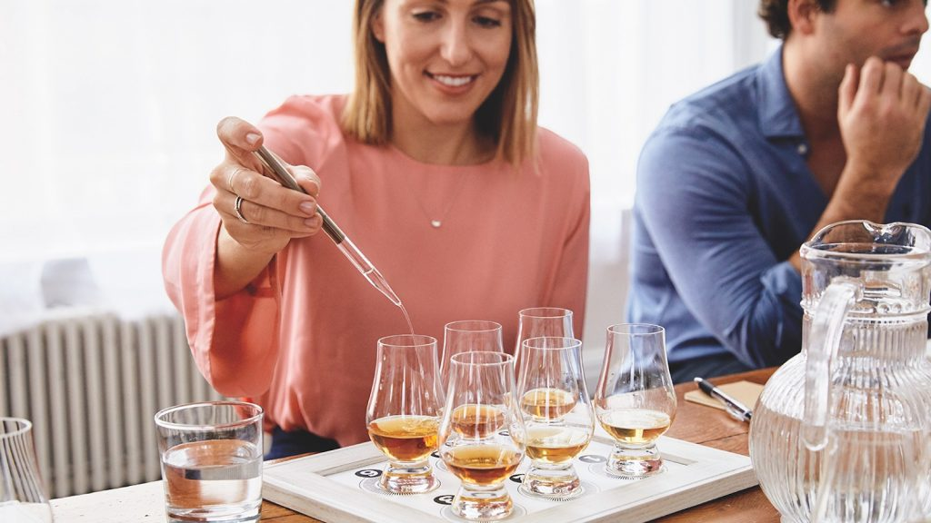 A woman uses a pipette to put water into her glass of whisky.