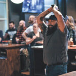 A bearded, tattooed fellow wearing a gray T-shirt, blue jeans, and dark hat gets ready to hurl an ax at a target at The Corner in Ferndale, Michigan, while people in the background socialize, drink what appears to be cans of beer, and, ostensibly, watch their friends throw axes at targets.
