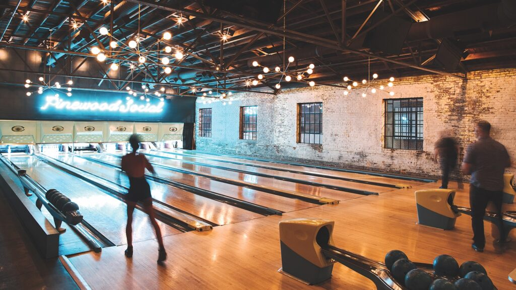 People bowl at six vintage bowling lanes at Pinewood Social, an industrial-looking bar and restaurant in Nashville, Tennessee with exposed brick walls and the name of the venue spelled out in fluorescent letters above the pins at the end of the lanes.