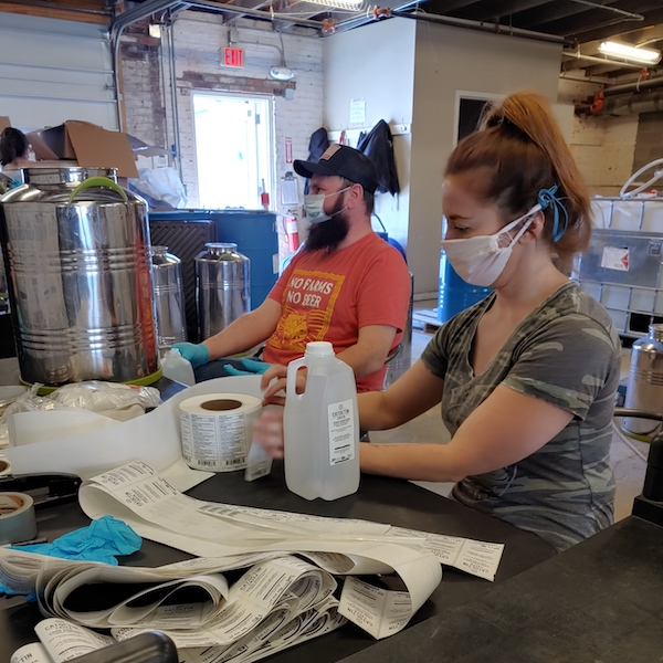 Purcellville, Virginia-based Catoctin Creek Distilling Co. brand ambassadors Steve Merlo and Lauren Barrett bottle hand sanitizer on March 31.