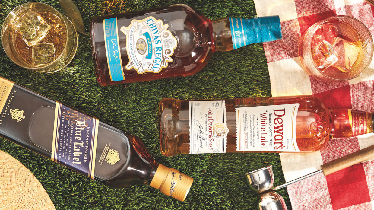 Bottles of blended scotch—Johnnie Walker Blue Label, Dewar's White Label, and Chivas Regal Mizunara—rest on their sides, pictured from a bird's-eye view, atop what appears to be close-cropped grass, next to a red and white plaid-patterned picnic blanket, along with a wooden-handled metal jigger, and two rocks glasses containing ice and what appears to be whisky cocktails; the brim of what appears to be a straw hat also is partially in view to the lower left corner of the photo.