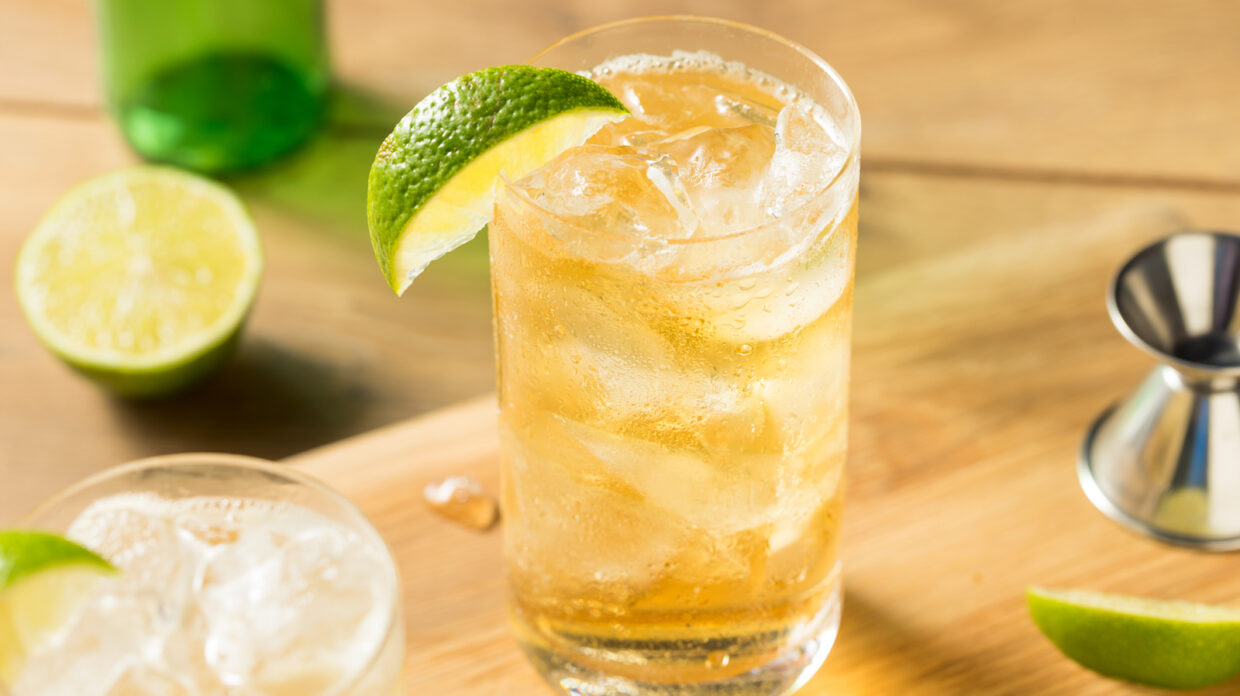 A Collins glass containing what appears could be blended scotch, gin, ginger beer, and lime juice, garnished with a lime wedge, rests on a wooden surface next to a jigger, more lime, and another glass.