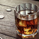 Whiskey with ice in crystal glass on wood table.