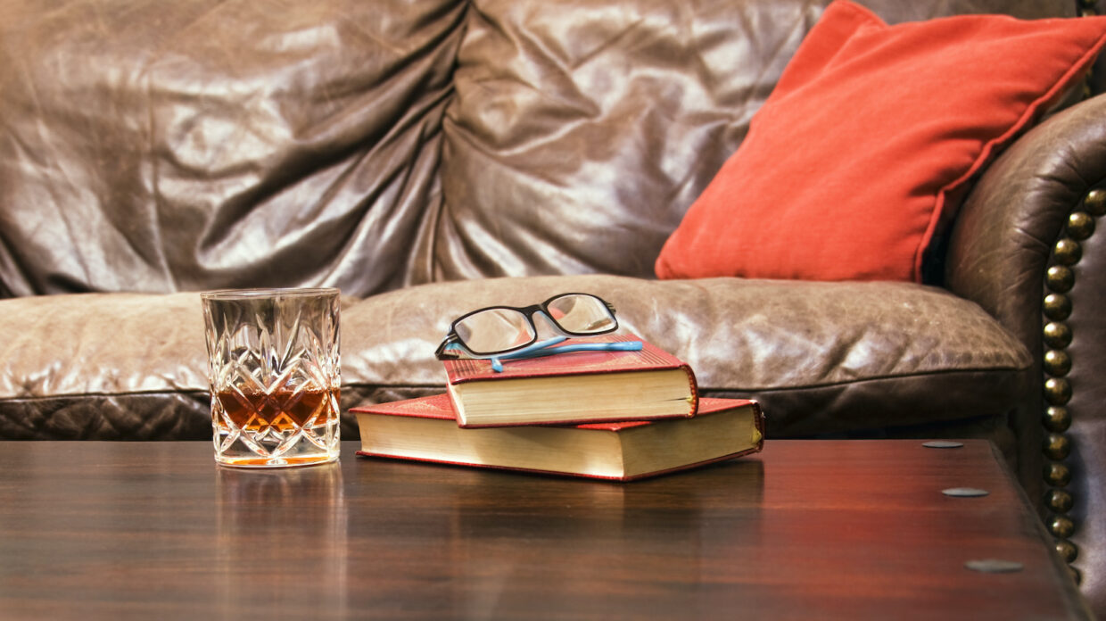 a relaxing scene two books with a pair of glasses and a crystal whisky glass