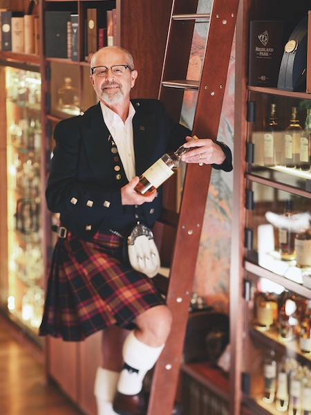 A kilted man holds a bottle of scotch while standing on a ladder.