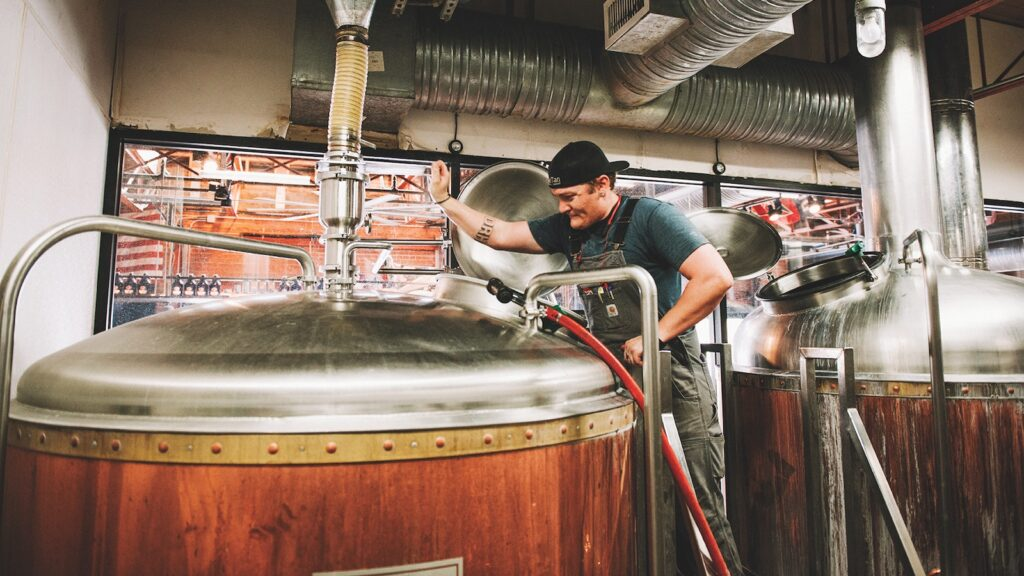 A man sees over a large vat at SanTan brewing company.