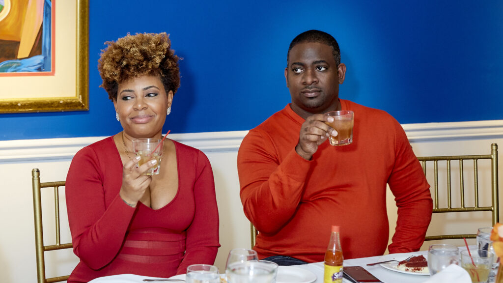 Black Bourbon Society founder and CEO Samara Rivers, in a red dress, and COO Armond Davis, in a brightly colored long-sleeved shirt, raise their glasses in a toast during a during a private dinner on Dec. 5, 2019, at Harlem soul food eatery Sylvia's in New York City.
