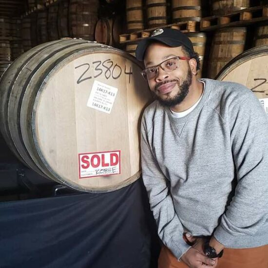 Jamar Mack, founder of Kentucky's Original Black Bourbon Enthusiasts, stands next to a whiskey barrel at Smooth Ambler's rickhouse in West Virginia in September 2019.