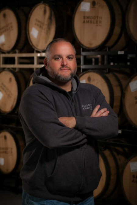 Smooth Ambler head distiller and CEO John Little stands with his arms crossed, wearing a gray Smooth Ambler hoodie, in front of Smooth Ambler whiskey barrels.