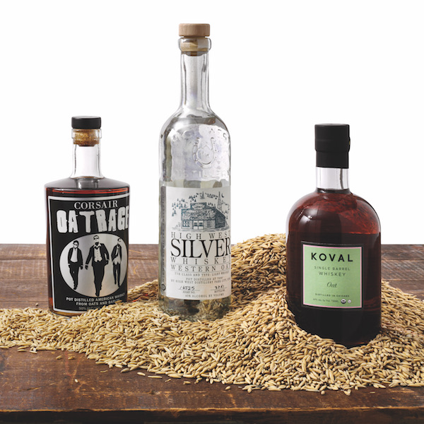 Three different oat whiskeys—Corsair Oatrage, High West Silver Western Oat, and Koval Single Barrel Oat—rest on a wooden surface with oats scattered in front of them.