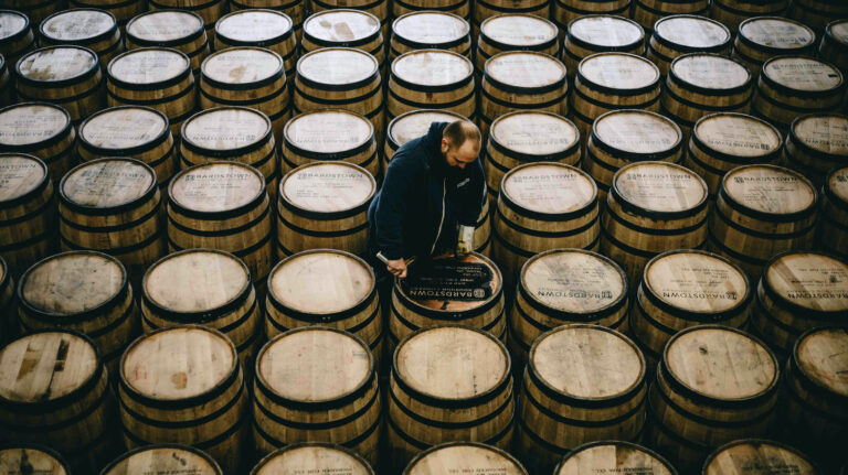 A man stands among many bourbon barrels.