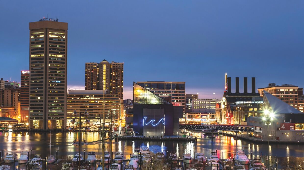 Baltimore Skyline inner harbor at twilight, National Aquarium (with neon wave), and boats in marina, Inner Harbor, Patapsco River, Baltimore, Maryland USA