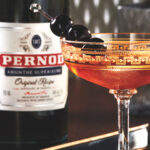 The auburn-hued Cocktail à la Louisiane, in a fancy chilled coupe, garnished with three speared maraschino cherries, rests on a dark tray, a bottle of Pernod Original Recipe absinthe visible in the background.