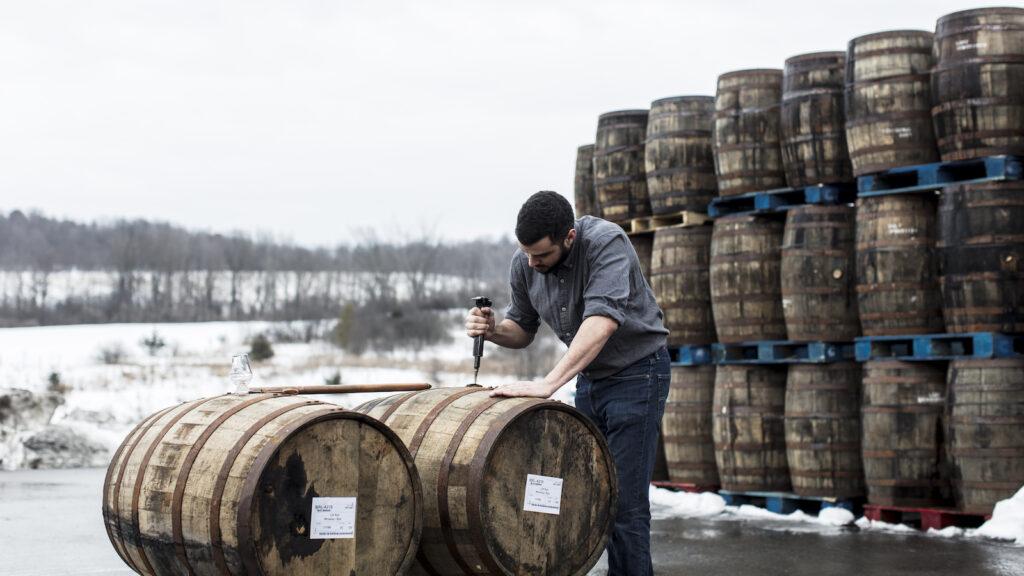 A man taps into a whiskey barrel.