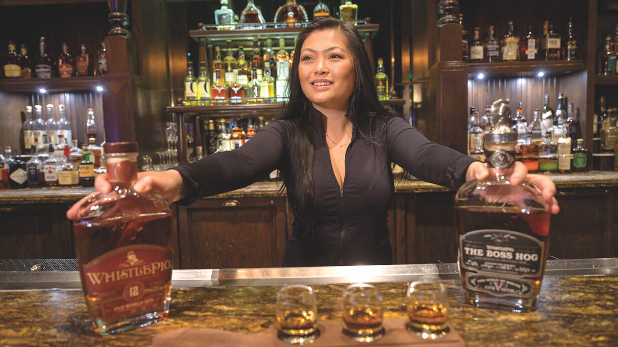 A woman, probably a bartender or bar manager, stands behind the bar at Whiskey Down at MGM Grand in Las Vegas, Nevada, her hands resting on bottles of WhistlePig whiskey on top of the bar, and between the bottles, a flight of whiskey consisting of three drams atop a wooden plank.