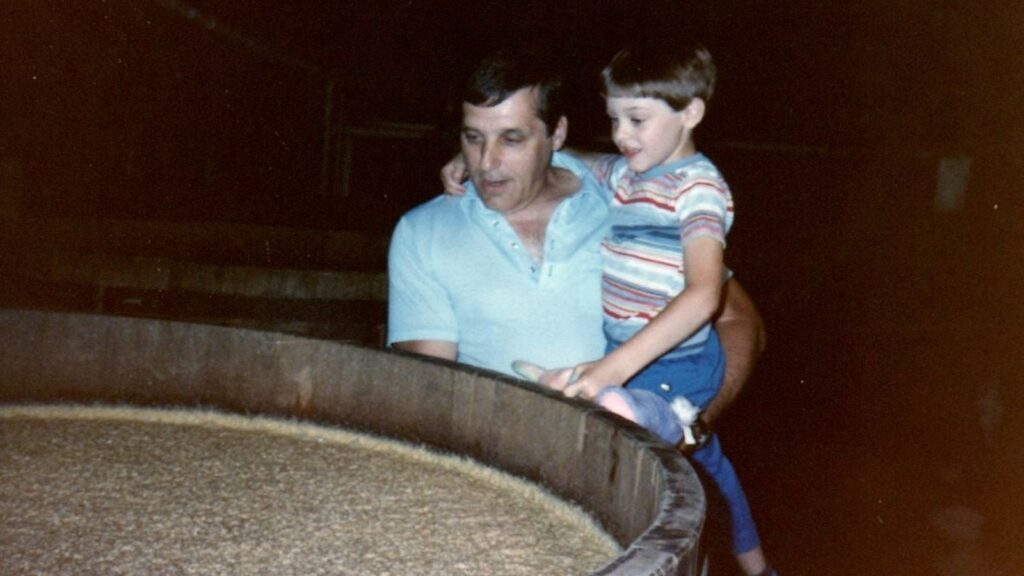 Dick Stoll holding his son, Josh, and looking into a fermenter