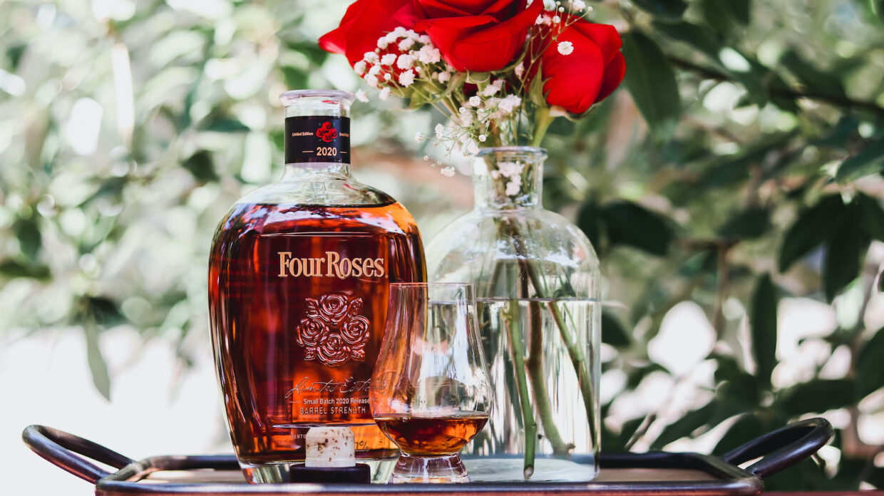 Bottle of Four Roses limited edition small batch 2020 with a glass, cork, and vase of roses