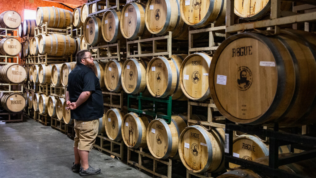 Jake Holshue—head distiller at Rogue Ales & Spirits in Newport, Oregon—stands in Rogue's ocean-adjacent warehouse, looking at, and surrounded by, barrels of Rogue spirits.