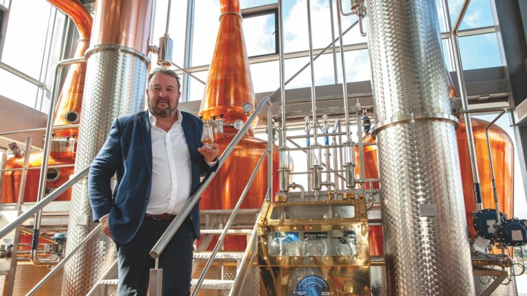 Michael Scully, owner of Clonakilty Distillery, holds a glass of whiskey in front of three pot stills.