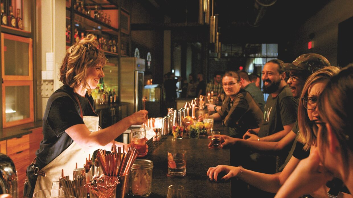 A woman mixes drinks for patrons at the bar at Michter's Fort Nelson Distillery