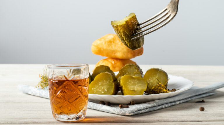 Glass of whisky with sliced pickles and biscuits