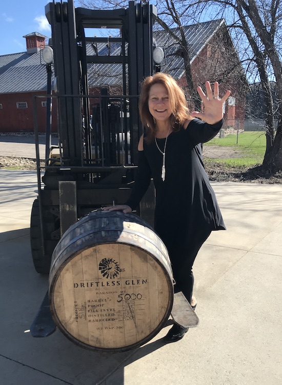 Renée Bemis, CEO and co-founder Baraboo, Wisconsin-based Driftless Glen Distillery, stands outside, next to a barrel, waving.
