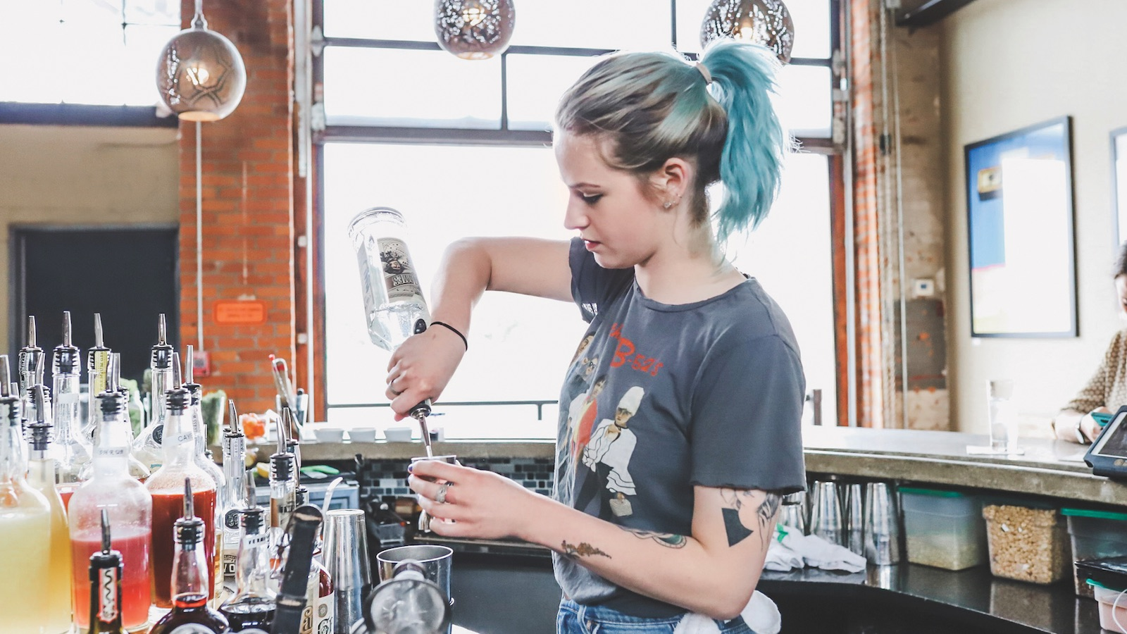 A woman mixes cocktails at the bar of Two James Spirits in Detroit