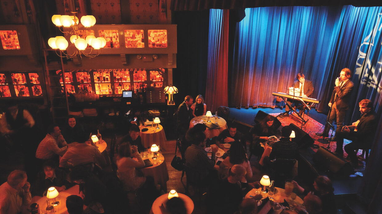 Diners sit at tables eating and drinking with small lamps casting a dim glow, while a three-person band performs onstage at the Flatiron Room in New York City. A chandelier hangs overhead and the bar is visible in the background, and behind it, many bottles of whisky rest on shelves in what appears to be glass cases.