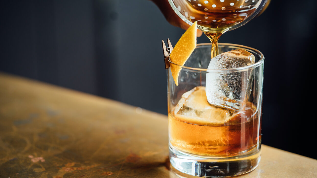A whiskey cocktail being poured into a rocks glass.