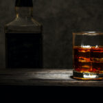 A glass of whiskey in a spotlight with an unidentified bottle in the shadows behind it