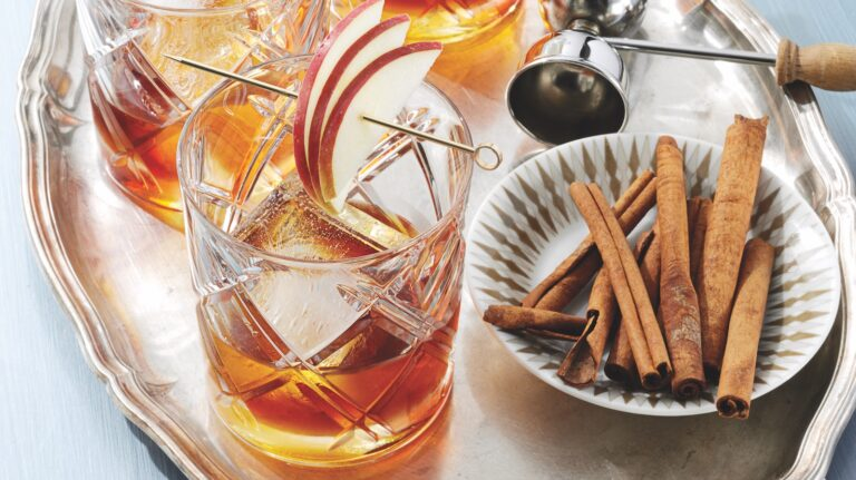 Two whiskey cocktails sit next to a small plate of cinnamon sticks.