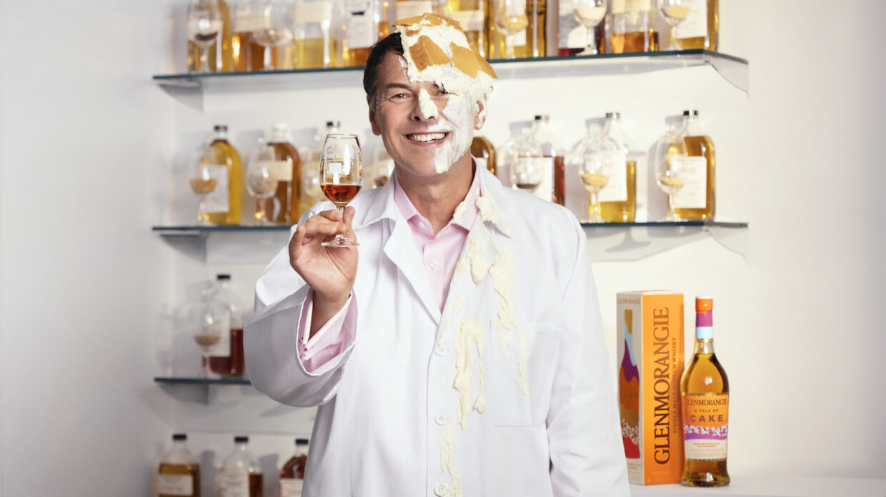 Dr. Bill Lumsden of Glenmorangie smiling and holding a glass of scotch with cake all over his face