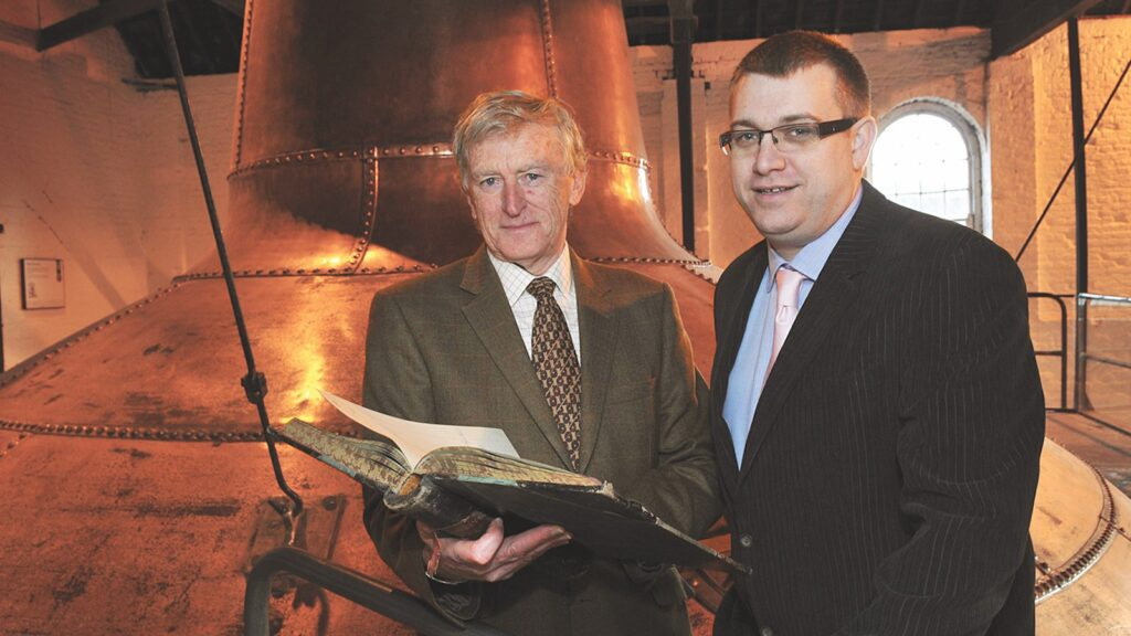 Barry Crockett and Brian Nation of Irish Distillers in front of a pot still