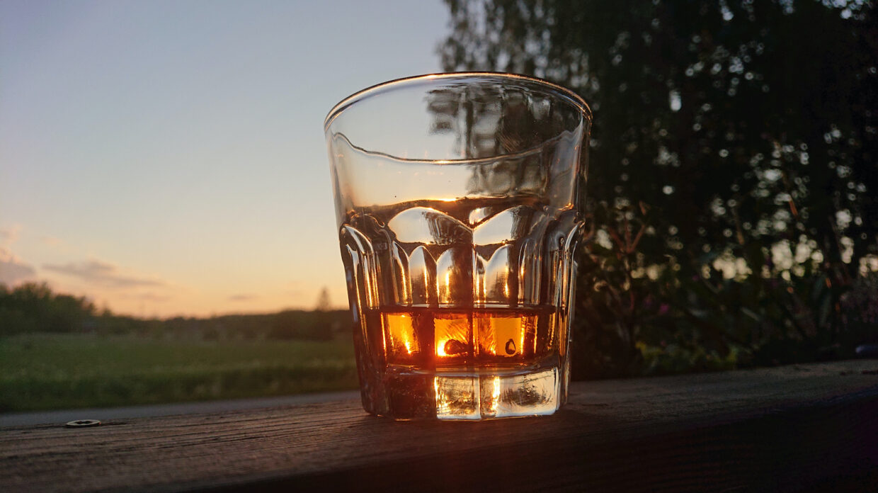 Close-Up Of Glass With Vhiskey On Table During Sunset