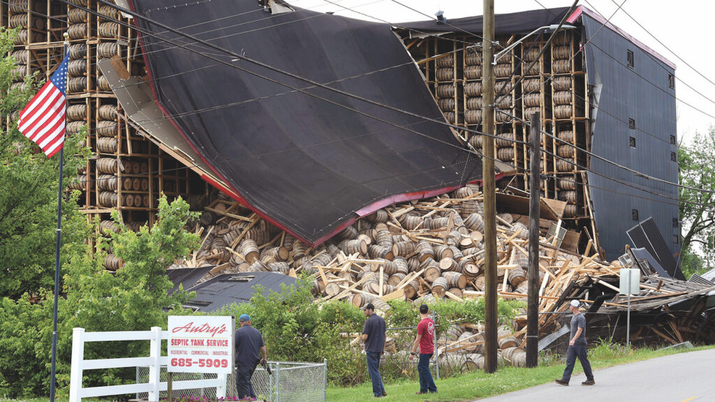 Workers from O.Z. Tyler Distillery look over Warehouse H, which collapsed during a thunderstorm shortly after midnight Monday, on June 17, 2019 in Owensboro, Kentucky.