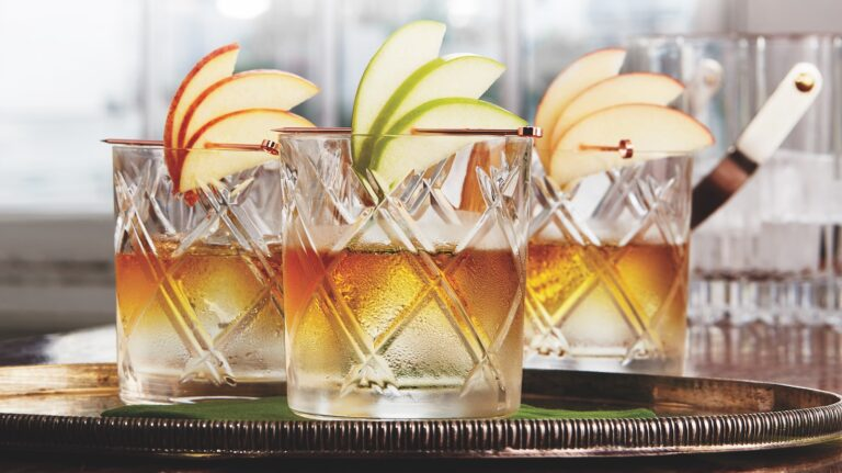 3 whiskey cocktails garnished with apple slices on a platter.