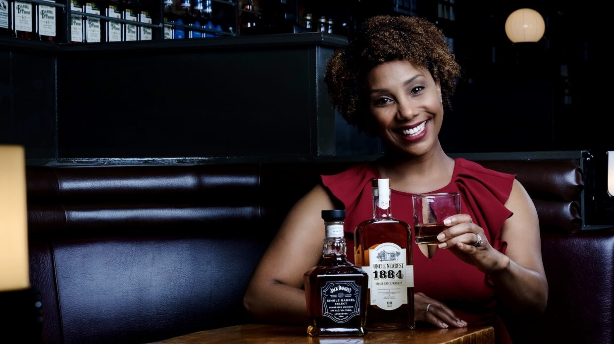 Tracie Franklin, Nearest & Jack Advancement Initiative's first distilling apprentice, poses with bottles of Jack Daniel's and Uncle Nearest whiskey.