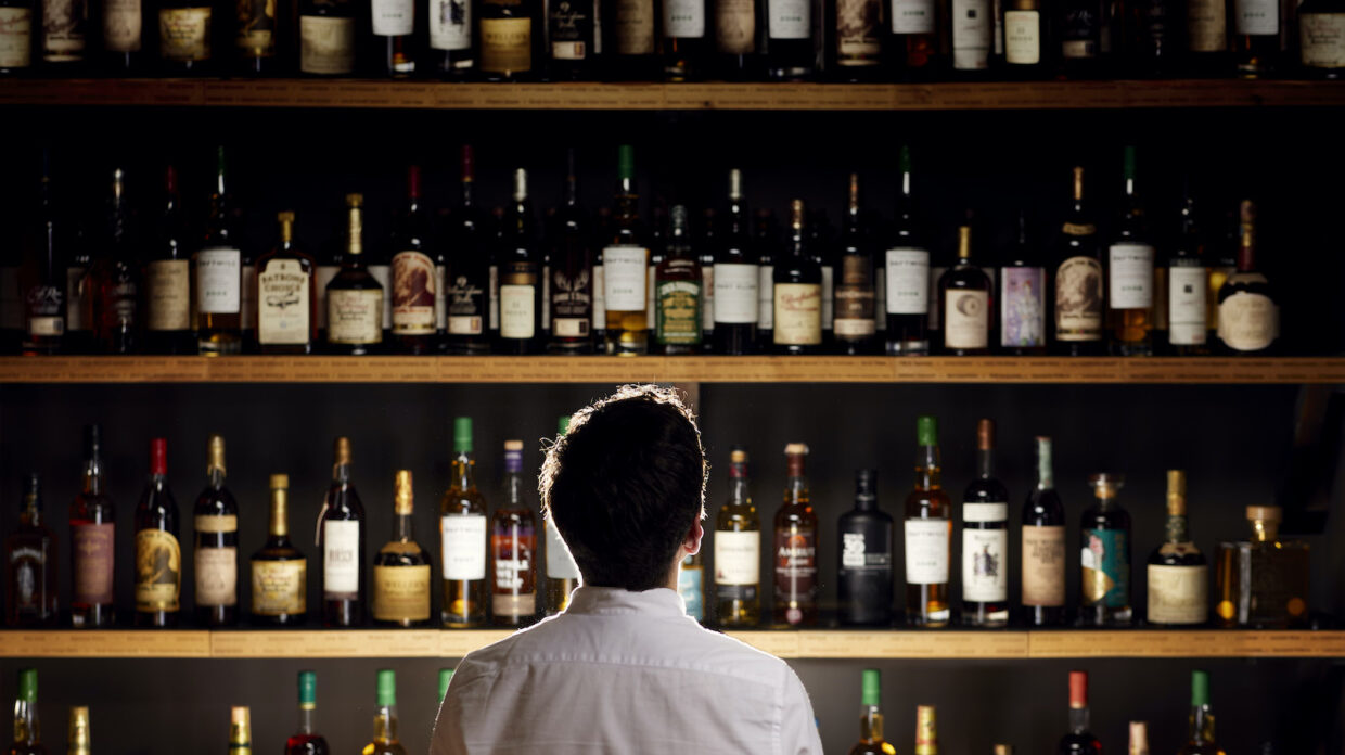 A man faces a wall of rare whisky bottles being auctioned by Whisky Auctioneer on behalf of a collector known only as Pat.