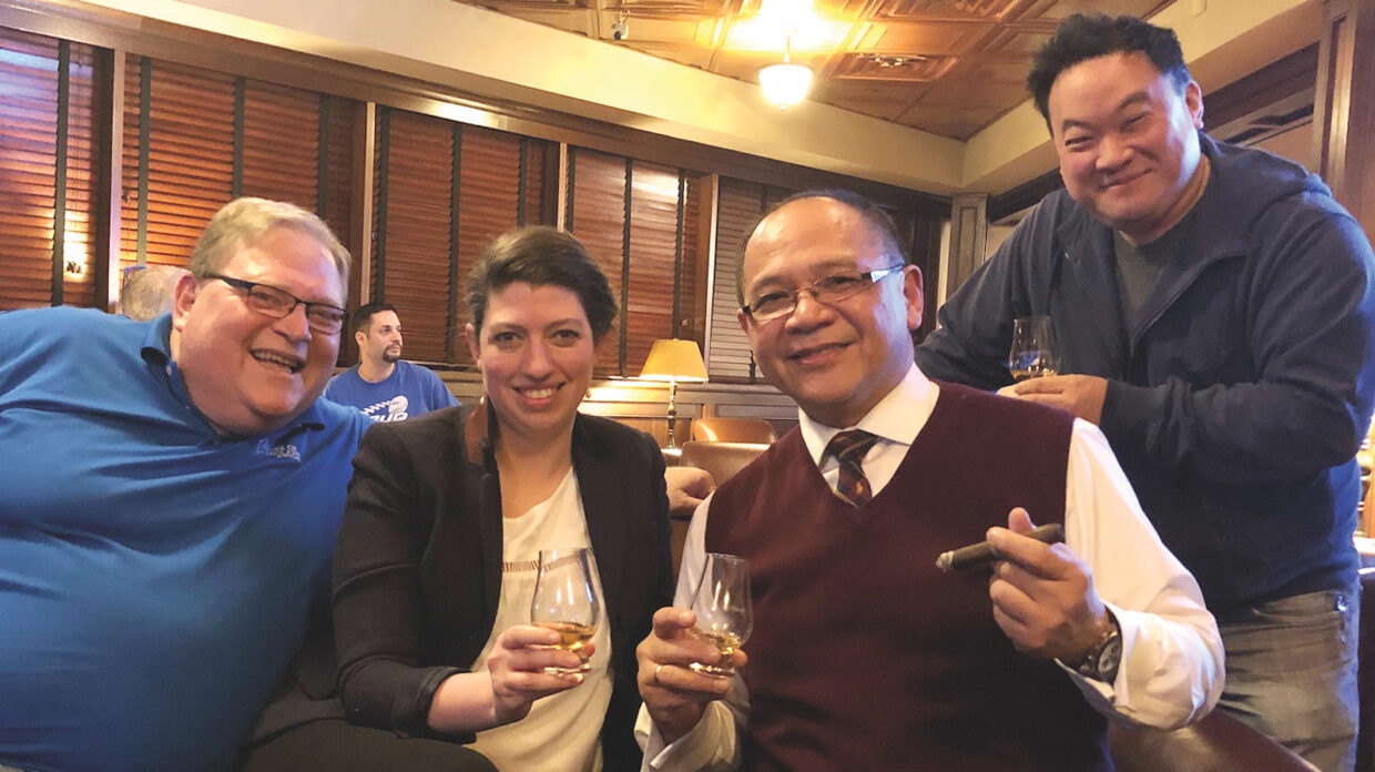 Whisky Blasphemy co-founder Jun Nunez, second from right, enjoys a cigar and whisky with fellow club members at Holt's Cigar Co., in Philadelphia.