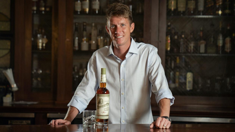 Dixon Dedman stands behind a bar with a bottle of Kentucky Owl.