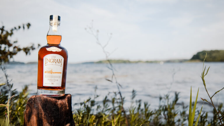 A bottle of O.H. Ingram River Aged straight whiskey rests upon a wooden stump amid vegetation, with what appears to be a river in the background.