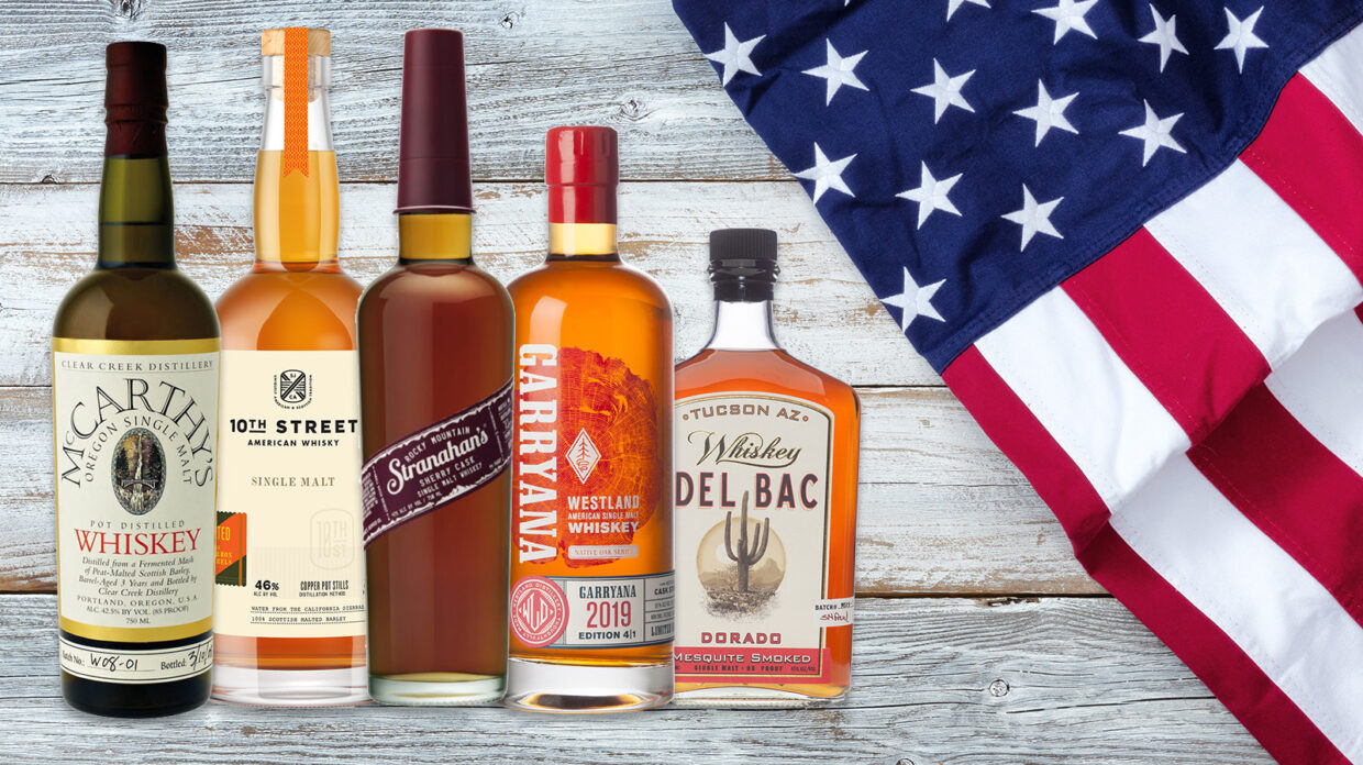 bottles of American single malt whiskey on a wood background with an American flag