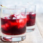 Two glasses with a cocktail and cherries in them.