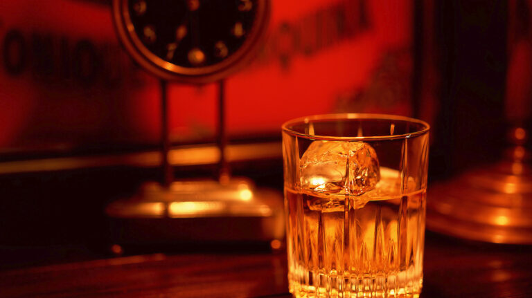A glass of whisky in front of a desk clock.