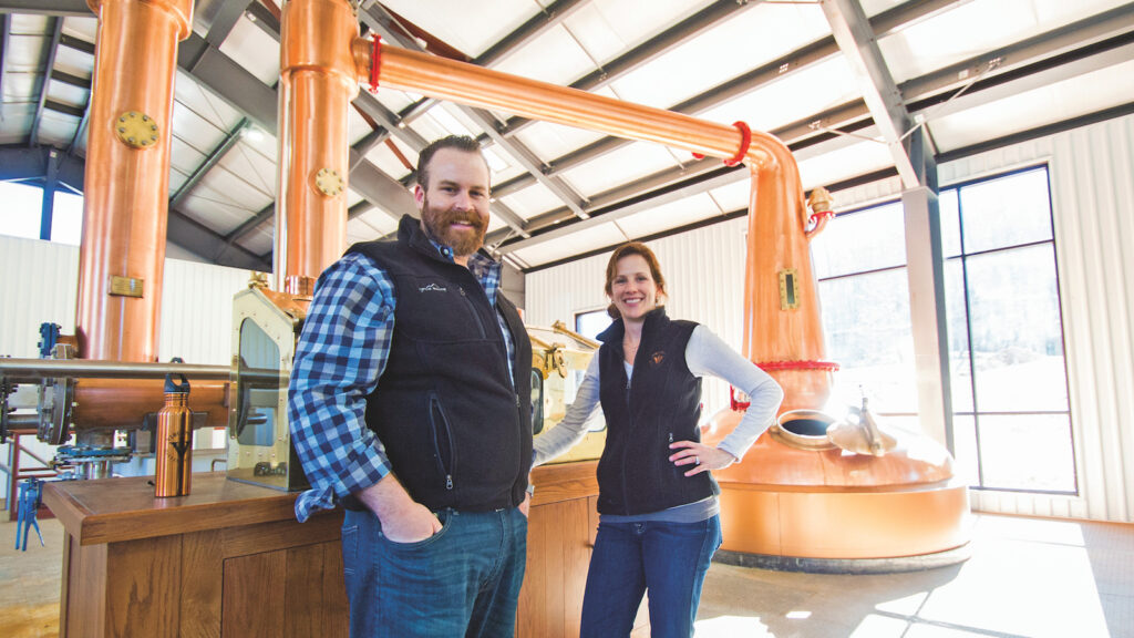 Virginia Distillery Co. owners Gareth and Maggie Moore at the distillery with a view of a still in the background.